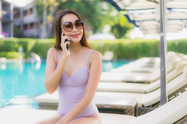 Il sorriso felice delle belle donne asiatiche del ritratto si rilassa intorno alla piscina nella località di soggiorno dell'hotel