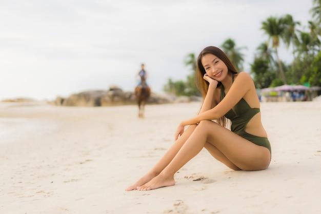 Il sorriso felice delle belle donne asiatiche del ritratto si rilassa sull'oceano tropicale del mare della spiaggia