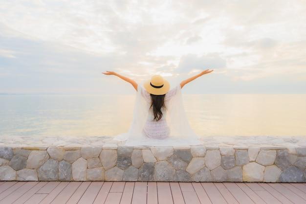 Il sorriso felice delle belle giovani donne asiatiche del ritratto si rilassa intorno all'oceano della spiaggia del mare