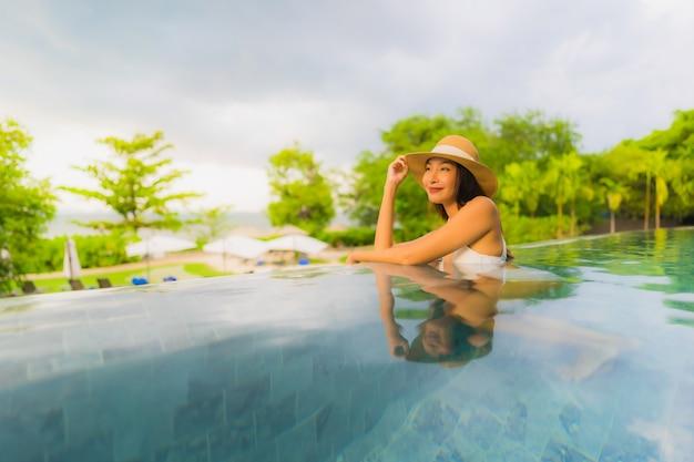 Il sorriso felice delle belle giovani donne asiatiche del ritratto si rilassa intorno alla piscina all'aperto in hotel