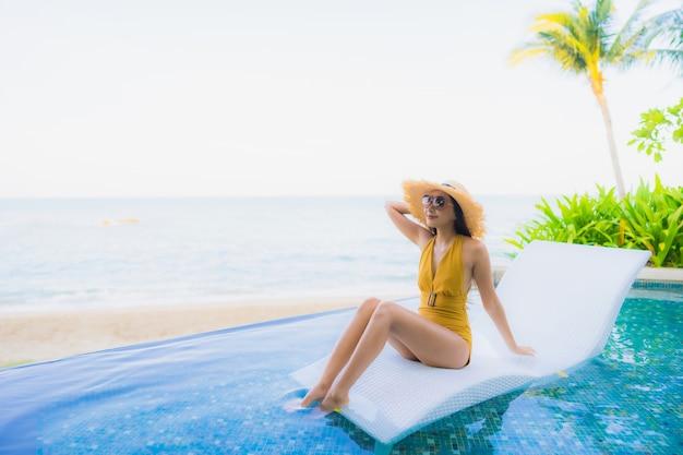 Il sorriso felice delle belle giovani donne asiatiche del ritratto si rilassa intorno alla piscina all'aperto