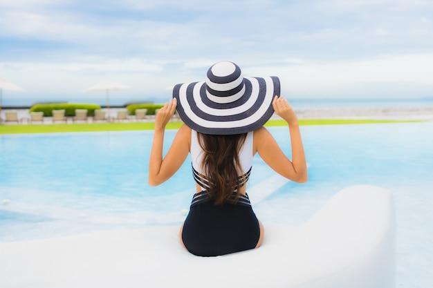 Il sorriso felice delle belle giovani donne asiatiche del ritratto si rilassa intorno alla piscina