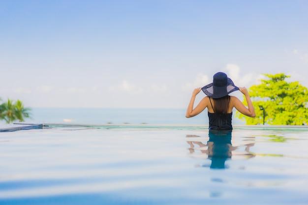 Il sorriso felice delle belle giovani donne asiatiche del ritratto si rilassa la piscina all'aperto in hotel