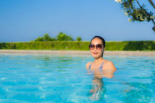 Il sorriso felice delle belle giovani donne asiatiche del ritratto si rilassa la piscina all'aperto nella località di soggiorno