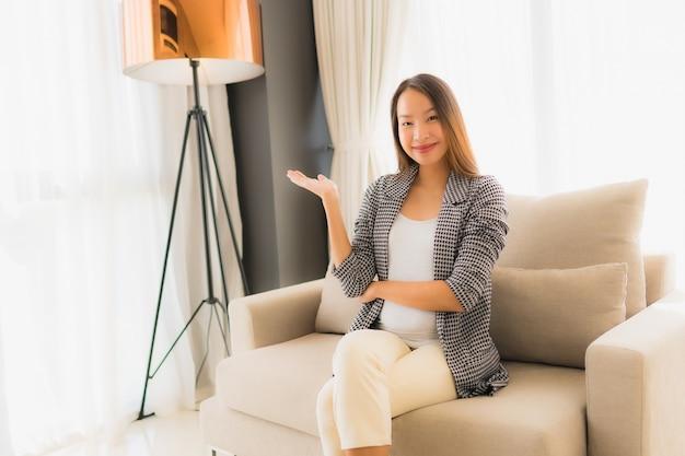 Il sorriso felice delle belle giovani donne asiatiche del ritratto si rilassa la seduta sulla sedia del sofà