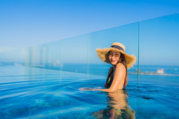 Il sorriso felice delle belle giovani donne asiatiche si rilassa intorno alla piscina all'aperto nella località di soggiorno dell'hotel per il viaggio nella vacanza di festa