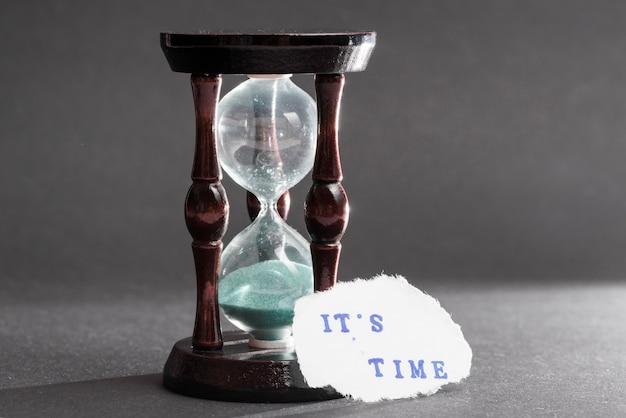 Il suo testo del tempo su carta strappata vicino al vetro ora su sfondo grigio