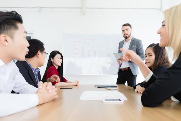 Il supervisore maschio sta spiegando i grafici delle prestazioni dell'azienda ai suoi dipendenti e agli altri impiegati nella sala riunioni dell'ufficio.