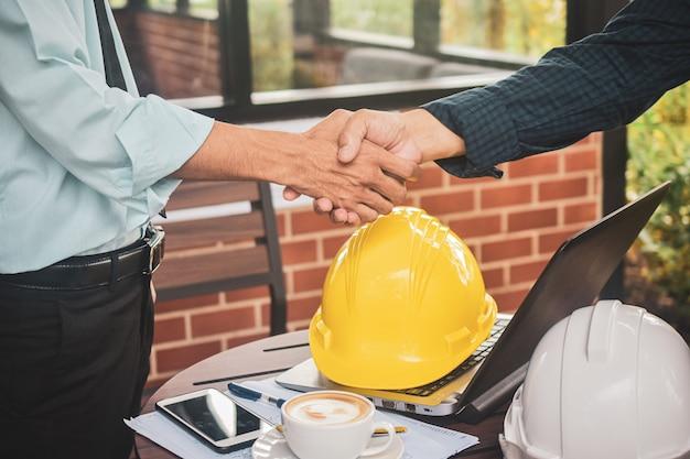 Il supervisore stringe l'area di lavoro del computer portatile del cappello duro di successo della costruzione di progetti di accordo del caporeparto, concetto di successo di scossa della mano