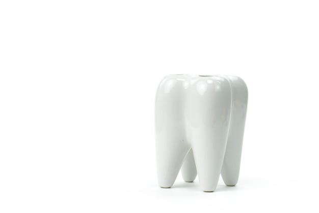 Il supporto dello spazzolino da denti ha modellato come superficie bianca isolata alta vicina del dente primario