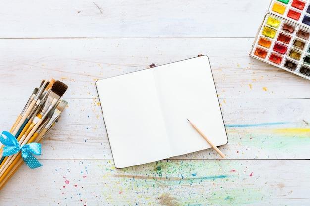 Il taccuino deride su con i rifornimenti di arte sulla tavola creativa di legno bianca. vista dall'alto