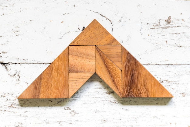 Il tangram imbarazza nella forma della freccia sul vecchio fondo di legno bianco