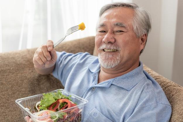 Il tatto dell'uomo senior di stile di vita felice gode di di mangiare l'insalata fresca dell'alimento di dieta sul sofà