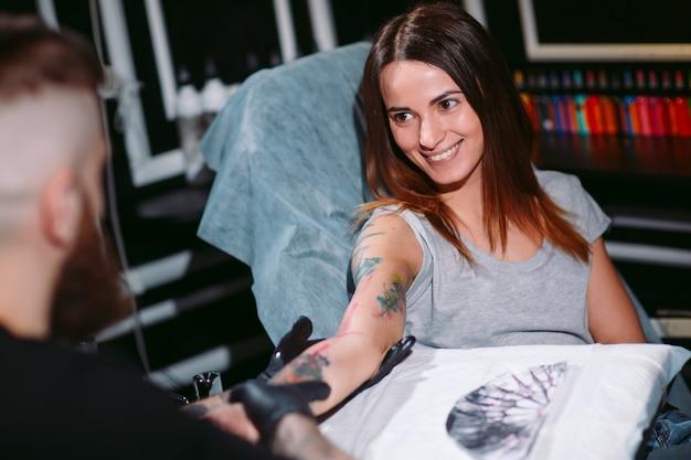 Il tatuatore professionista fa il tatuaggio su una ragazza.