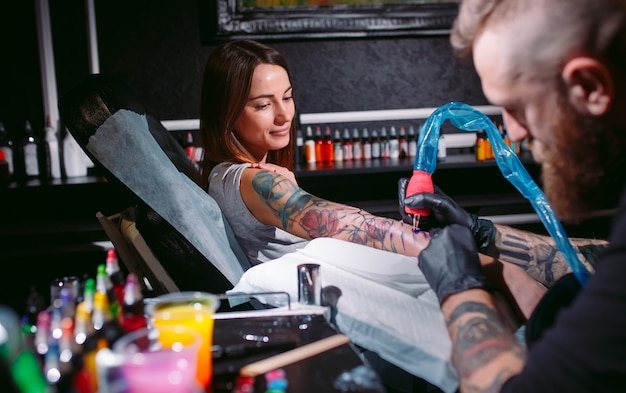 Il tatuatore professionista fa un tatuaggio sulla mano di una ragazza.
