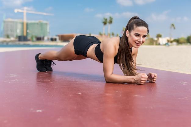 Il tavolato sorridente della donna della spiaggia di forma fisica che fa l'yoga si esercita. ragazza felice che prepara i suoi addominali che esercitano i suoi muscoli centrali con la posa della plancia.