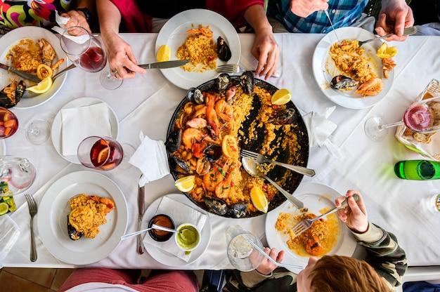 Il tavolo del ristorante con paella spagnola ai frutti di mare è servito in padella. gamberetti freschi, scampi, cozze, calamari, polpi e capesante. vista dall'alto. ristorante