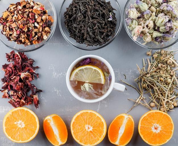 Il tè al limone in una tazza con arance, erbe piatte giaceva su una superficie di gesso
