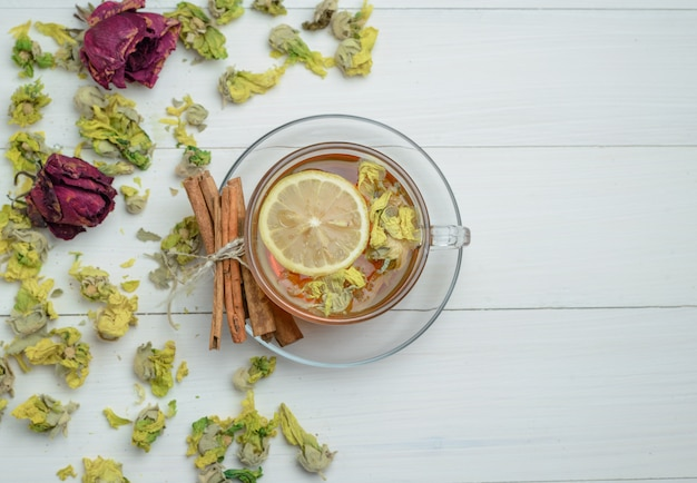Il tè al limone in una tazza con erbe secche, bastoncini di cannella distesi su una superficie di legno