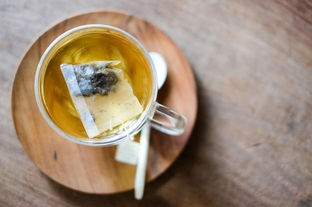 Il tè caldo alla lavanda in vetro serve con un cucchiaio di legno e un piattino