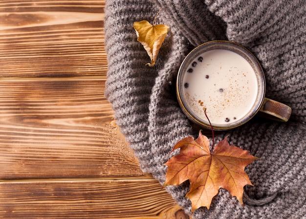 Il tè masala autunnale è una bevanda indiana tradizionale con latte su un tavolo di legno accanto a una sciarpa e foglie grigie a maglia.