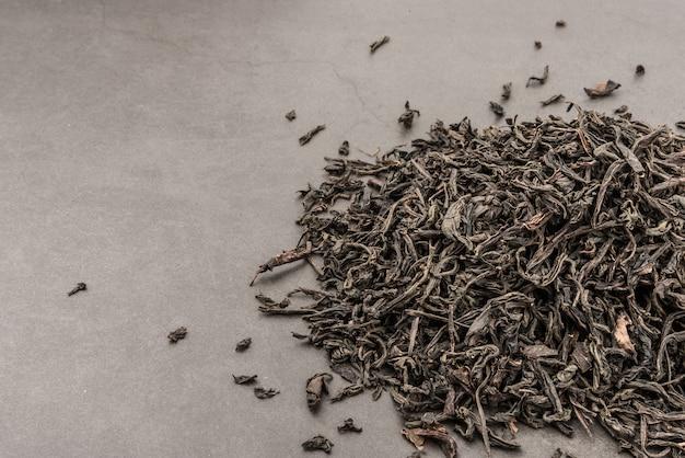 Il tè secco è versato sparso su una priorità bassa strutturata grigia.