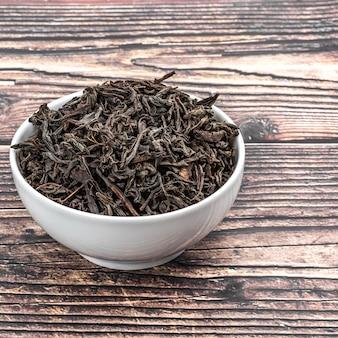 Il tè secco viene versato in una tazza di ceramica su un tavolo di legno.