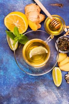 Il tè verde caldo in una tazza di vetro è servito con il limone, lo zenzero, la limetta, il miele e la menta sul fondo di legno blu di lerciume. vista dall'alto.