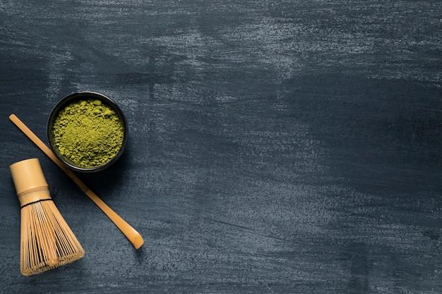 Il tè verde isolato vista superiore accanto alla frusta tradizionale