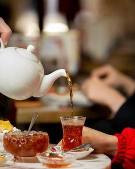Il tè versato nel bicchiere armudu dalla teiera servito con marmellata