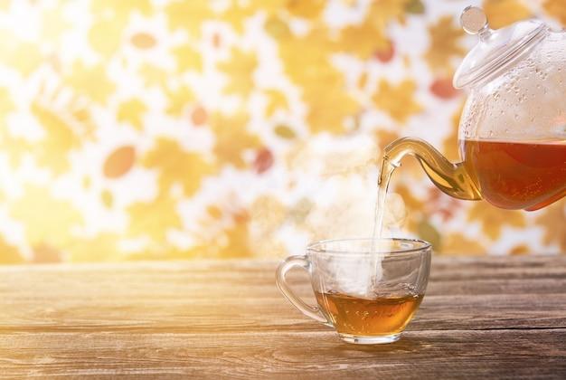 Il tè viene versato in una tazza di vetro sul tavolo di legno scuro, autunno