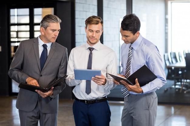 Il team aziendale interagisce utilizzando la tavoletta digitale e l'organizzatore in ufficio