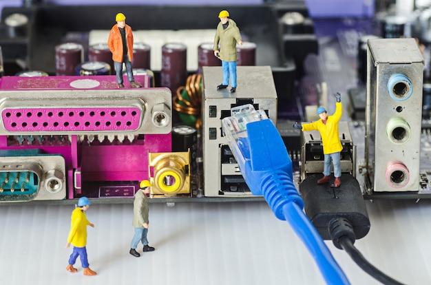 Il team di ingegneri in miniatura tenta di collegare i cavi ethernet alla porta