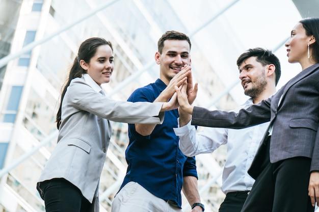Il team di uomini d'affari collabora per raggiungere l'obiettivo di successo nel costruire sullo sfondo della città