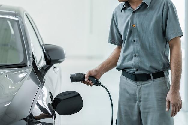 Il tecnico asiatico senior sta caricando l'auto elettrica o il veicolo elettrico nel centro servizi per manutenzione