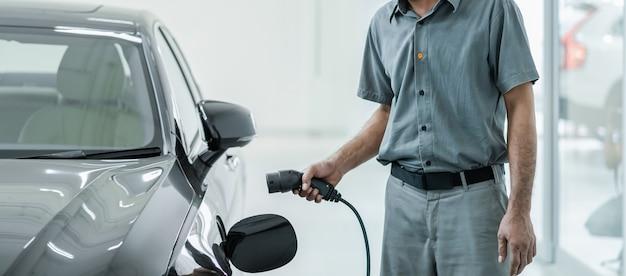 Il tecnico asiatico senior sta caricando l'automobile elettrica o il veicolo elettrico nel centro di servizio per manutenzione, concetto ecologico di energia alternativa