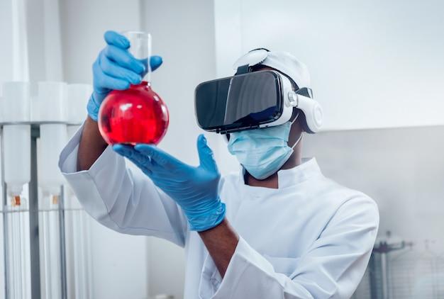 Il tecnico di scienza in vetri di realtà virtuale esamina la droga in laboratorio.