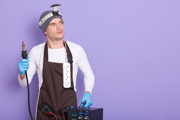 Il tecnico è pronto a saldare qualcosa, il maschio attraente indossa camicia casual bianca, cappello e grembiule marrone, tiene il saldatore