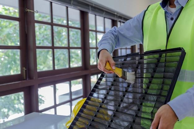Il tecnico pulisce e ripara il condizionatore d'aria della parete
