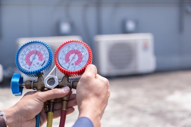Il tecnico sta controllando il condizionatore d'aria, misurando l'attrezzatura per il riempimento dei condizionatori d'aria.