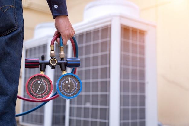 Il tecnico sta controllando il condizionatore d'aria, misurando le apparecchiature per il riempimento dei condizionatori d'aria.