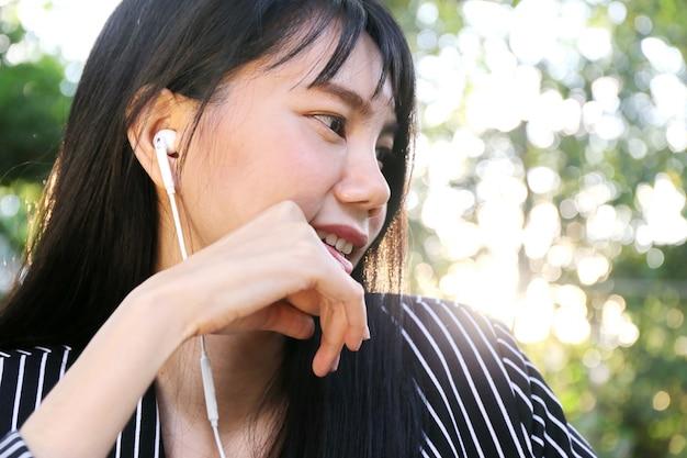 Il telefono asiatico di uso della mano della donna di affari della bella pelle abbronzata affascinante ed ascolta la musica di canzone dalla cuffia nella sala. presentando il tuo prodotto