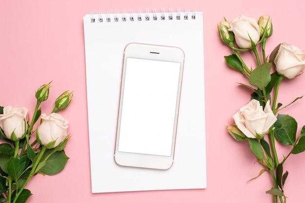 Il telefono cellulare con un taccuino bianco e le rose fiorisce su fondo rosa