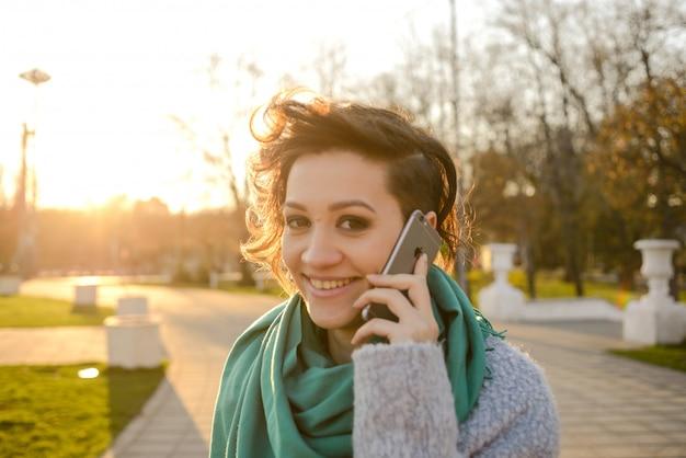 Il telefono di uso della giovane donna mentre cammina per lavorare al mattino permuta in città