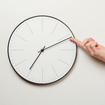 Il tempo di arresto della mano della donna sull'orologio rotondo, dito femminile prende la freccia minuta dell'orologio indietro, gestione di tempo e concetto di termine