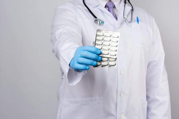 Il terapeuta medico adulto è vestito con un cappotto bianco uniforme e guanti sterili blu è in piedi e in possesso di una pila di pillole
