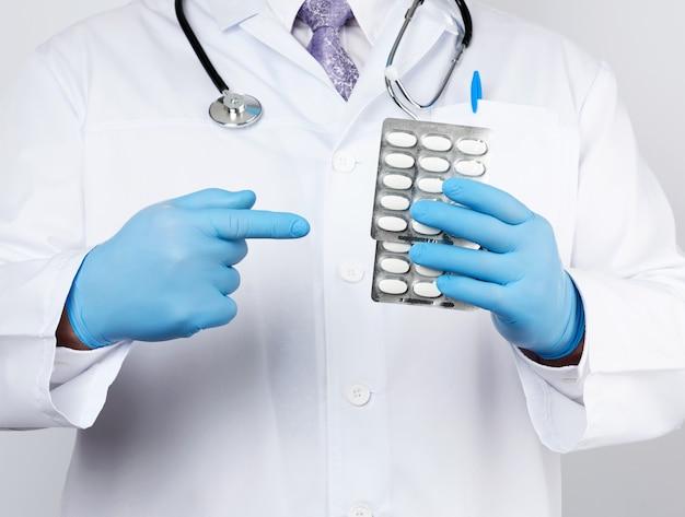 Il terapeuta medico adulto è vestito con un cappotto bianco uniforme e guanti sterili blu è in piedi e tiene una pila di pillole in blister
