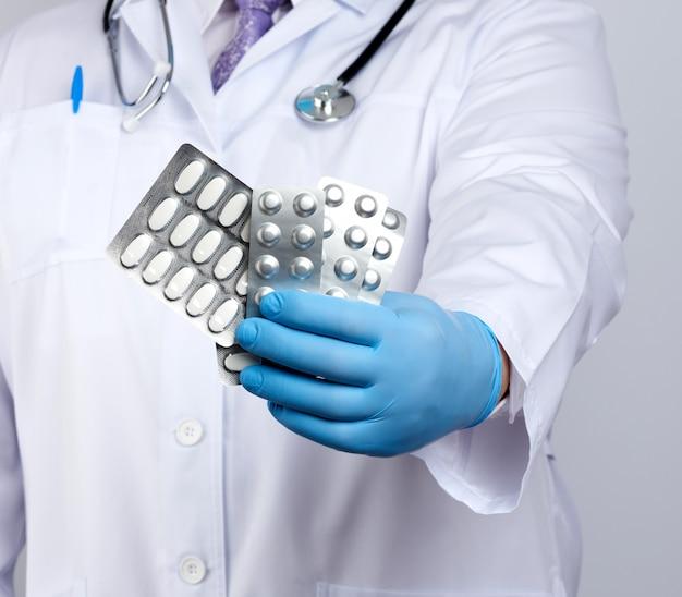 Il terapista medico è vestito con un cappotto bianco uniforme e guanti sterili blu è in piedi e con in mano una pila di pillole in blister