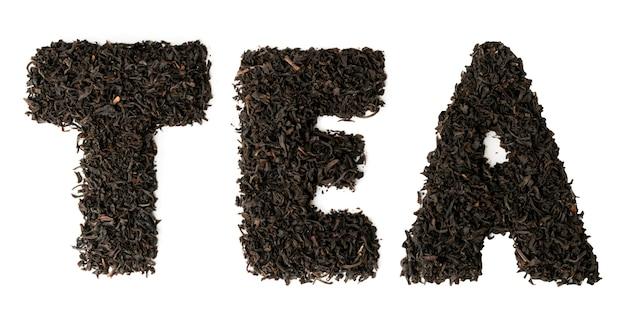 Il testo è disposto tè dalle foglie di tè nero su bianco. vista dall'alto.