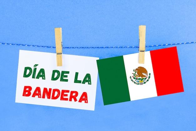 Il testo in spagnolo: il giorno della bandiera. testo con la bandiera del messico.
